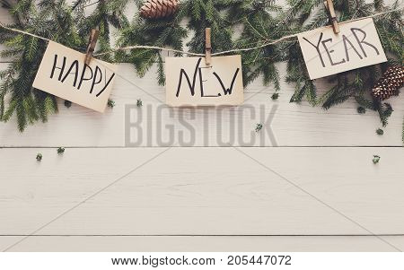 Happy new year decoration, garland frame concept background, top view with copy space on white wood table surface. Winter holidays celebration border from fir tree branches and pine cones