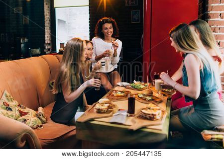 Group of young girlfriends having lunch in fast food restaurant eating craft hamburgers.