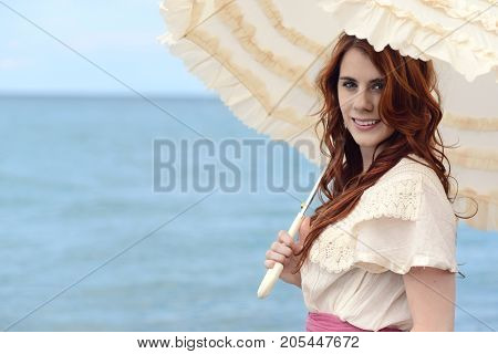 portrait vintage woman with parasol by ocean