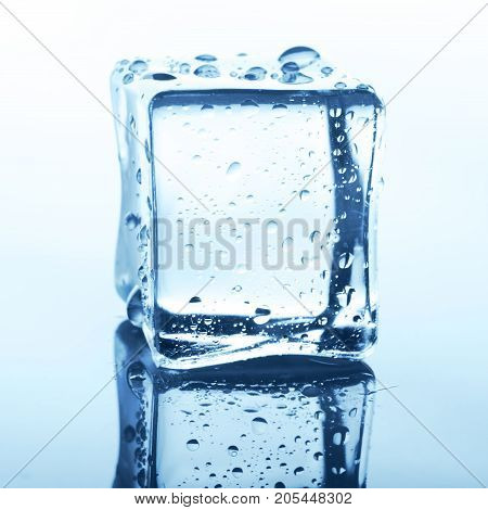 Transparent ice cube with reflection on white background. Closeup of cold crystal block cutout