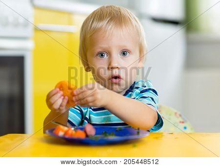 Little kid boy eating healthy food at home or nursery