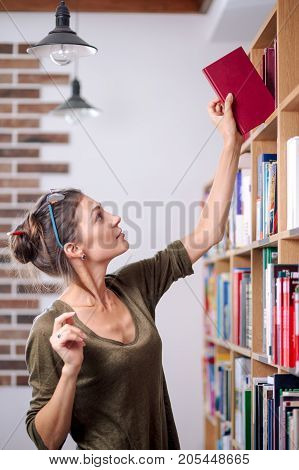 Young attractive woman, wearing glasses and cotton blouse, is delighted to find the wanted book on the colorful bookshelf, in a library.