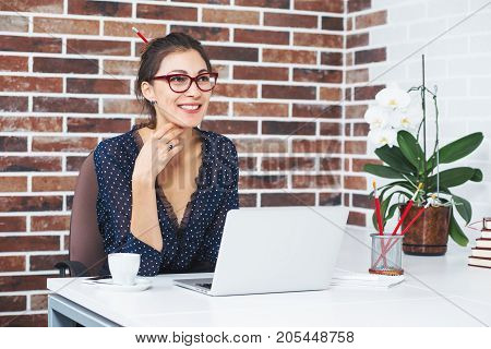 Portrait of smiling businesswoman with glasses and laptop, wearing blouse with dots and a pencil in hair, sitting at her workplace in office looking at somebody while touching chin with arm.