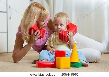 cute mother and kid boy role playing together indoor