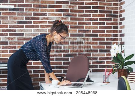Business woman wearing glasses, blouse with dots and pencil skirt staying near a desk looking to laptop screen with fingers on touchpad on a office brick background. Designer with pencil in her bun.