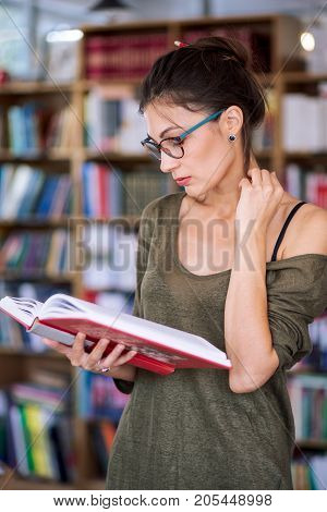 Young simpatic woman wearing fashionable colorful glasses and one shoulder cotton blouse holding a book in hands while reading it on a bookshelf background, playing with hair, in a library.