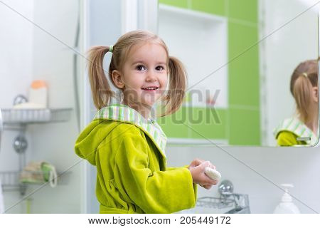 cute little girl with ponytail in green bathrobe washing her hands in bathroom