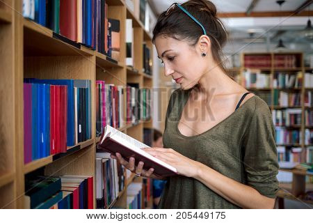 Young simpatic woman wearing fashionable colorful glasses on head and one shoulder cotton blouse holding a book in hands while reading it on a bookshelf background, in a library.