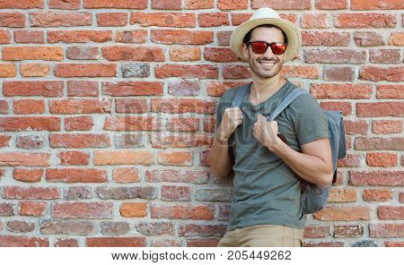 Сloseup Portrait Of Sporty Tourist Man Pictured Against Red Brick Background On Summer Day Wearing S