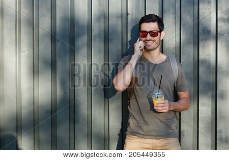 Outdoor Closeup Of Young Trendy Caucasian Male Standing With Backpack Pressed To Gray Wooden Backgro