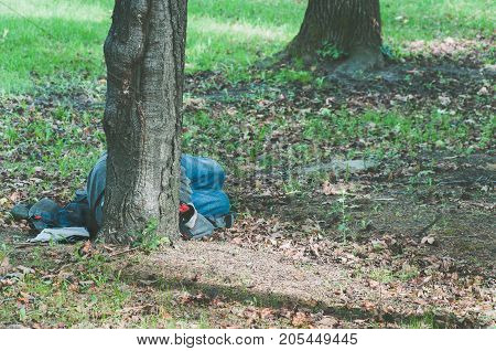 Poor homeless refugee man sleeps on the ground of the park in the city