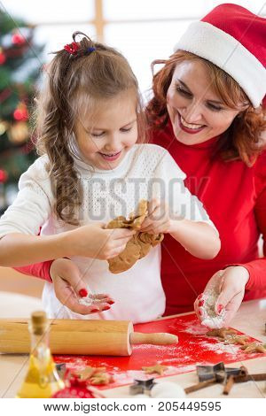 Child girl with her mother baking Christmas cookies in the kitchen