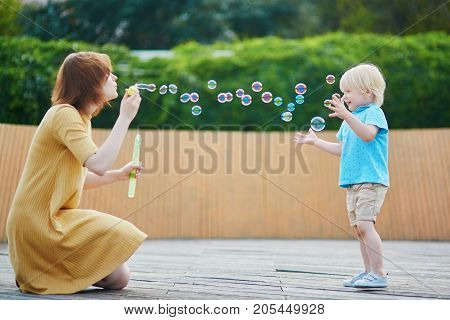 Mother Blowing Bubbles And Playing With Her Little Son