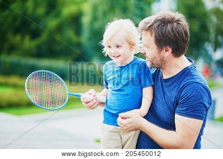 Little Boy Playing Badminton With Dad On The Playground