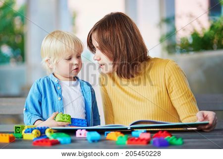 Young Mother Reading Book To Her Son