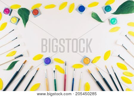 Watercolor and brushes at beige background. Flat lay, top view. Art and education concept.