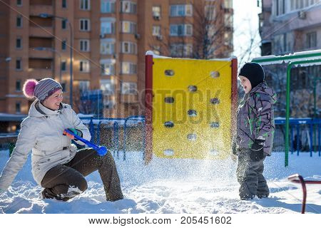 Mother and son enjoying beautiful winter day outdoors playing with snow at winter time. In big city at playground.