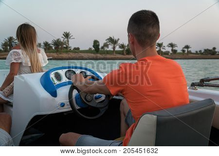 The guy drives a motor boat on the channels of the city of El Gouna.