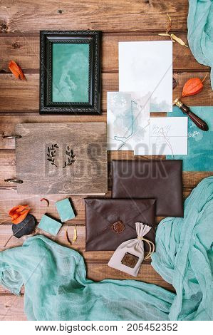 presents, congratulation, marriage concept. complete set of wedding polygraphy presented by few leather envelopes with wax seal, albom with magnificent wooden cover, frame for photo and some sheets
