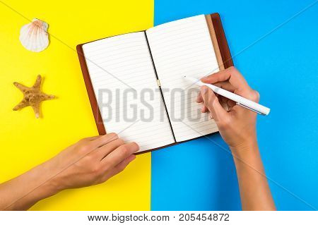 Travel, vacation, summer concept. Woman hand writing in notebook over blue and yellow background.