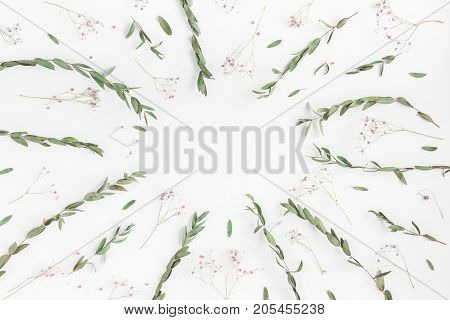 Flowers composition. Frame made of pink flowers and eucalyptus branches on white background. Flat lay top view copy space
