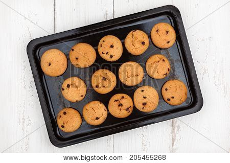 Old baking tray with homemade peanut cookies on wooden background top view