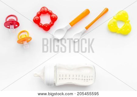 children feeding with breastmilk or infant formula powdered baby milk and toys on white table background top view