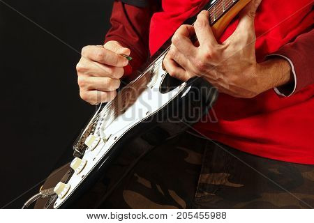 Rock musician put fingers for chords on electric guitar on the black background