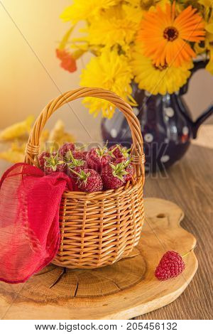 Basket with ripe fragrant raspberries and a beautiful autumn bouquet. Yellow and orange flowers in the jar. The red berries on the table. The concept of autumn.
