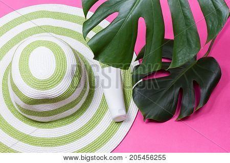 on green monstera leaf with sunglasses and straw hat on pink marble table