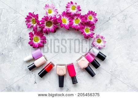 Choose nail polish for manicure. Bottles of colored polish on grey background top view.