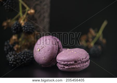 Sweet macaroons with blackberries on black bacground.