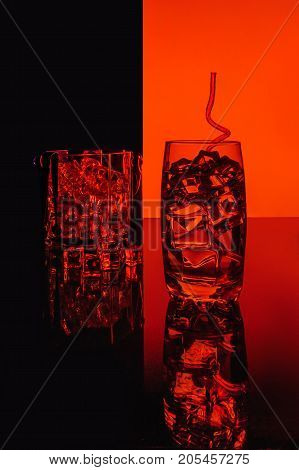 glass with water with ice cubes on a red round background