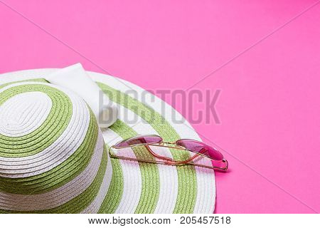Straw hat and sun block lotion tube and sunglasses on a pink background
