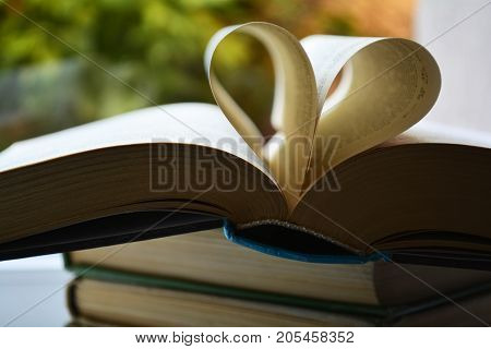 opened old book with a bookmark in the shape of a heart on the window