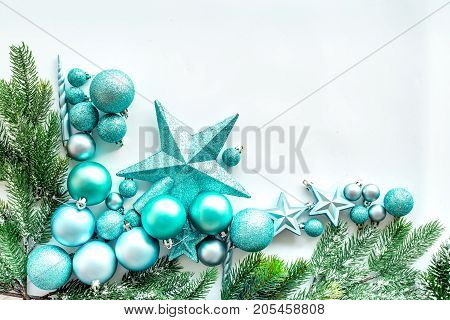 Christmas toys pattern. Blue stars and balls near pine branches on white background top view.