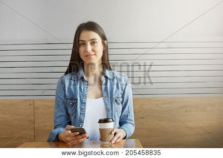 Attractive young girl with dark hair and stylish clothes sitting in cafe, drinking coffee and looking through photos from vacation on her smartphone