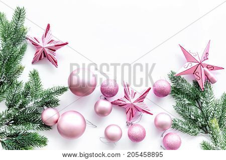 Christmas toys pattern. Pink stars near pine branches on white background top view.