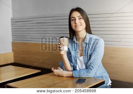 Cheerful woman with dark hair in trendy clothes sitting in cafeteria, drink coffee after long day at work, dreamy looking aside and thinking about things she did today. Lifestyle concept