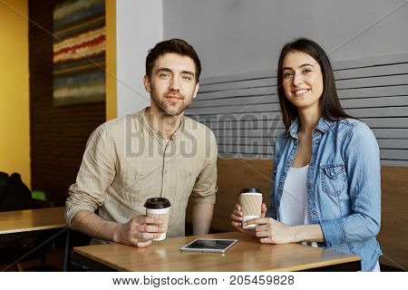 Two beautiful young students sitting in cafeteria, drinking cocoa, smiling, looking in camera posing for university newspaper article.