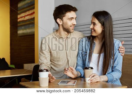 Happy young couple of two stylish students sitting in cafeteria, drinking coffee, smiling, hugging and talking about their life