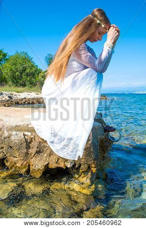 A young beautiful woman standing at the ocean in the summer.