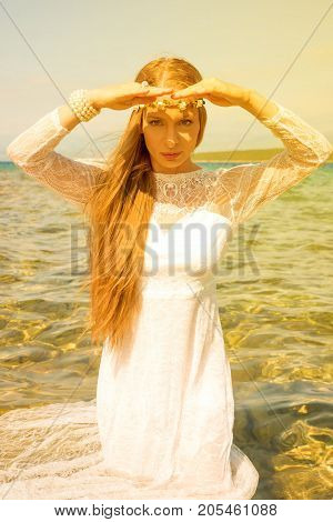 Young beautiful woman standing in the ocean in a wedding dress in the summer daylight.