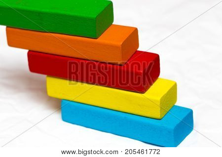 Ladder Made From Colorful Wooden Blocks On A White Background. The Concept Of Success, Victories And
