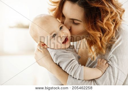 Close up portrait of young attractive mother kissing his crying baby. Kid looking aside with frightened face expression. Family concept