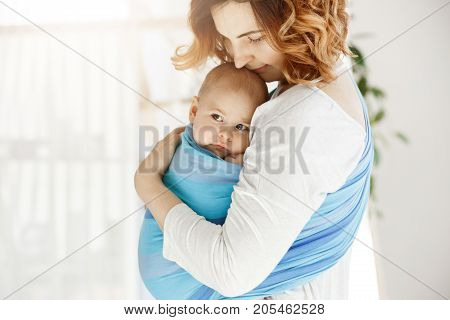 Portrait of beautiful young mother holding tight her newborn baby boy with love and caring. She smiling and feeling happiness of maternity moments