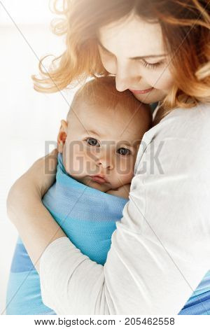 Close up of sweet little baby boy looking at camera with his big grey eyes. Mom snuggle her child with tenderness and love. Family concept