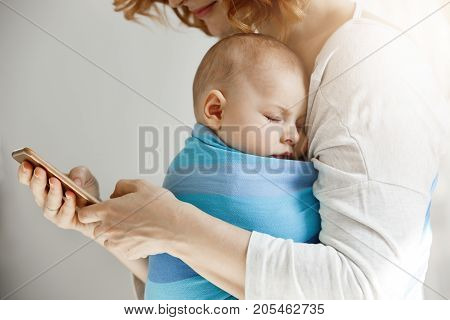 Beautiful young mother reads articles about maternity life on phone while little lovely son sleeping on her chest in blue baby slim