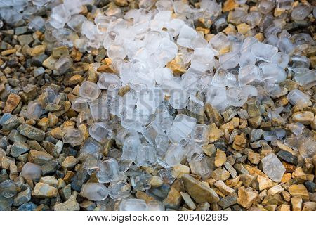 Close up of ice cubes on the ground gravel