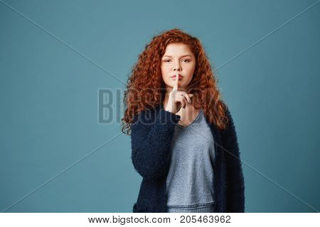 Portrait of good-looking ginger student girl with wavy hair holding index finger in front of lips showing friend not to tell story she said